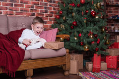 男孩在礼物醒了并且高兴 免版税库存图片