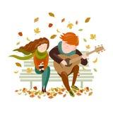 男孩在秋天公园弹一个女孩的吉他 库存图片