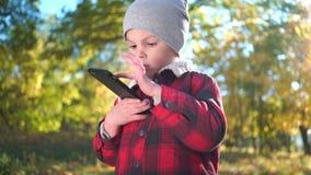 男孩在秋天公园打在智能手机的比赛 影视素材