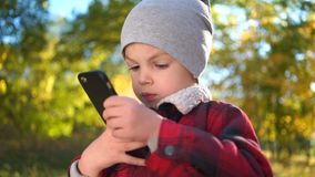 男孩在秋天公园打在智能手机的比赛 股票录像
