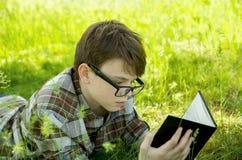 男孩在绿草说谎在公园并且读书 放松,户外 库存图片
