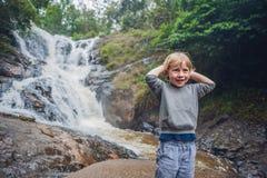 男孩在美丽的落下的Datanla瀑布背景中在山镇大叻,越南 免版税库存照片