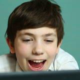 男孩在膝上型计算机的戏剧比赛,笑的使用 图库摄影