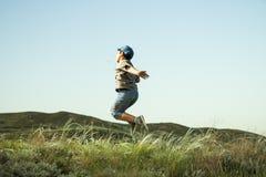 男孩在草在小山的背景中跳 图库摄影