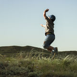男孩在草在小山的背景中跳 库存图片