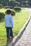 男孩在草走 免版税库存照片