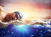 男孩在蓝色深水游泳 库存照片