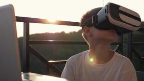 男孩在虚拟现实玻璃的计算机上使用在日落在日落 概念的现代