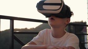 男孩在虚拟现实玻璃的计算机上使用在日落在日落 概念的现代 股票录像
