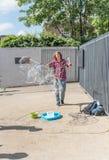 年轻男孩在街道做巨大的肥皂泡 图库摄影