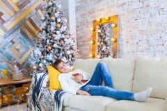 男孩在读圣诞节书的长沙发的10年 Xmas假日概念 免版税图库摄影