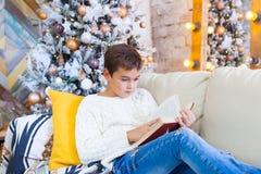 男孩在读圣诞节书的长沙发的10年 Xmas假日概念 免版税库存图片