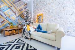 男孩在读圣诞节书的长沙发的10年 Xmas假日概念 图库摄影