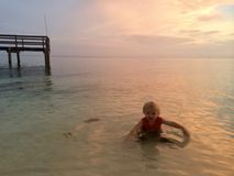 男孩在象加勒比的水中漂浮在日落在佛罗里达群岛 免版税库存照片