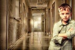 男孩在走廊站立对墙壁 库存图片