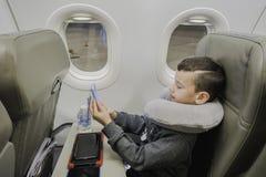 男孩在飞机坐在与旅行枕头的舷窗附近,使用在小配件和等待的起飞 免版税库存照片