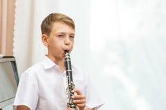 男孩在黑钢琴附近播放单簧管由窗口 音乐学、音乐教育和教育 库存图片