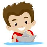 男孩在水中的演奏纸小船 库存照片