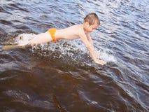 男孩在水中跳 库存图片