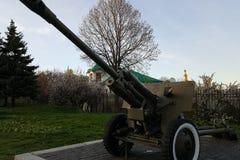 男孩在从二战的时代的一门大重的大炮播放在纪念碑的对苏联士兵 库存照片