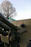 男孩在从二战的时代的一门大重的大炮播放在纪念碑的对苏联士兵 免版税库存照片