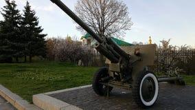 男孩在从二战的时代的一门大重的大炮播放在纪念碑的对苏联士兵 库存图片