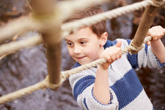 男孩在索桥的横穿小河在活动中心 免版税图库摄影