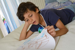 男孩在他的屋子观看的漫画里 图库摄影