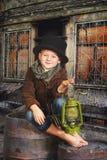 男孩在他的手上拿着一盏老煤油灯 纵向减速火箭风格化 库存图片
