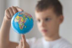 男孩在他的手上的举行玩具globus 库存图片