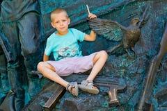 男孩在他的手上的拿着一只鸠 免版税库存图片
