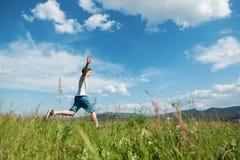 男孩在绿草跳 免版税库存图片