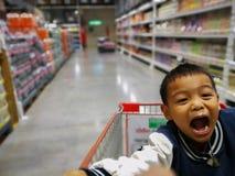 男孩在Supermaket 坐在购物车的男孩 免版税图库摄影