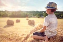 男孩坐一个干草堆在观看日落的夏天 库存照片