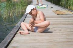 男孩坐一个木地板,牙拉扯从他的脚的一根刺 免版税库存图片