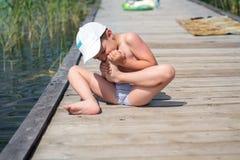 男孩坐一个木地板,牙拉扯从他的脚的一根刺 免版税库存照片