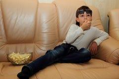 男孩坐一个沙发用玉米花和观看的电视与兴趣 库存图片