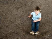 男孩坐一个石森林地路径 图库摄影
