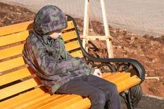 男孩坐一条长凳在公园并且抓与石头的长凳 免版税库存照片