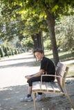 男孩坐一条长凳在公园 免版税库存照片