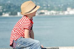 男孩坐与帽子的海滩,并且镶边T恤杉,调查距离 侧视图 免版税库存图片