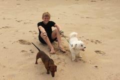 男孩坐与狗的海滩 库存图片