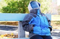 年轻男孩坐与他的被盖的面孔的一条长凳 免版税库存图片