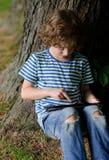 男孩坐倾斜反对大老树树干并且看片剂屏幕 免版税库存图片