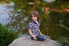 男孩坐冰砾在美丽如画的池塘 免版税图库摄影