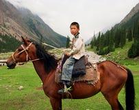 男孩坐在一个谷的一匹马在中亚之间山  免版税库存照片