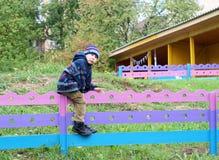 男孩坐在操场的木篱芭 免版税库存照片