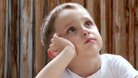 男孩坐在桌上并且拿着他的头用他的手,孩子认为并且作梦 孩子等待 影视素材