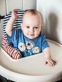 男孩坐在椅子的七个月 免版税图库摄影