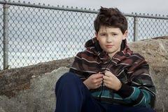 年轻男孩坐在链节篱芭前面的一个岩石在多云灰色天空下 库存照片